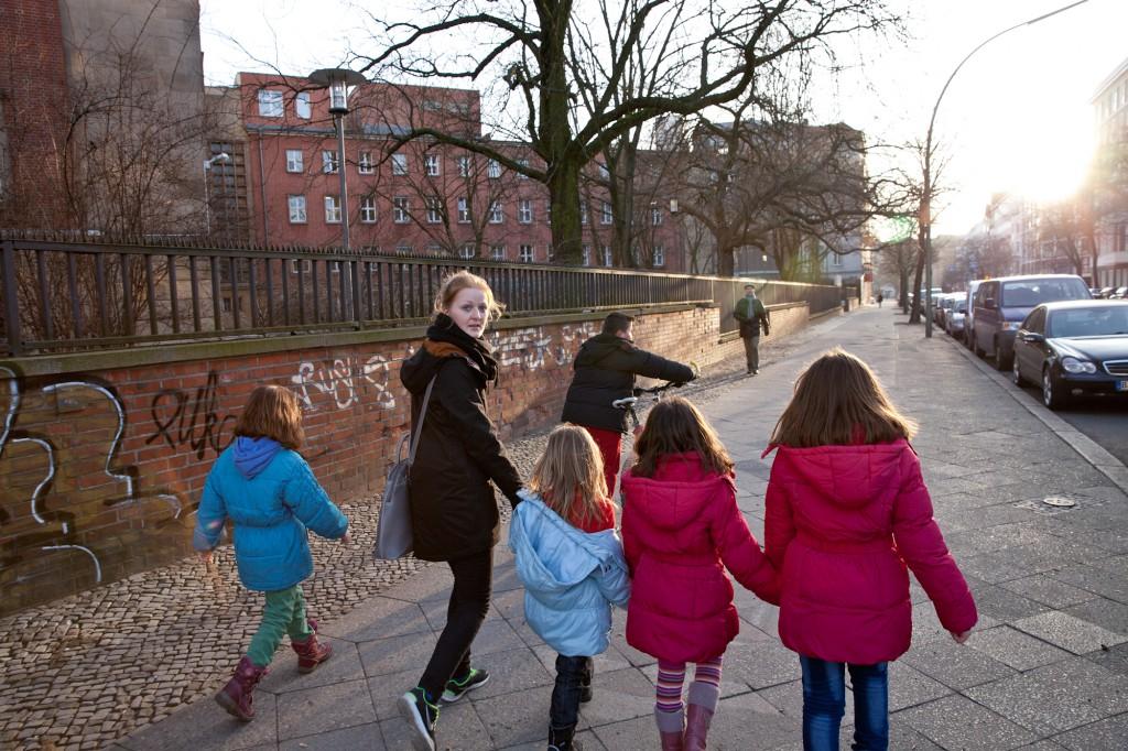 Freiwillige Helfer bringen die Kinder quer durch die Stadt von der Notunterkunft zum Sportunterrich. (c) Harms/Franquesa 2015