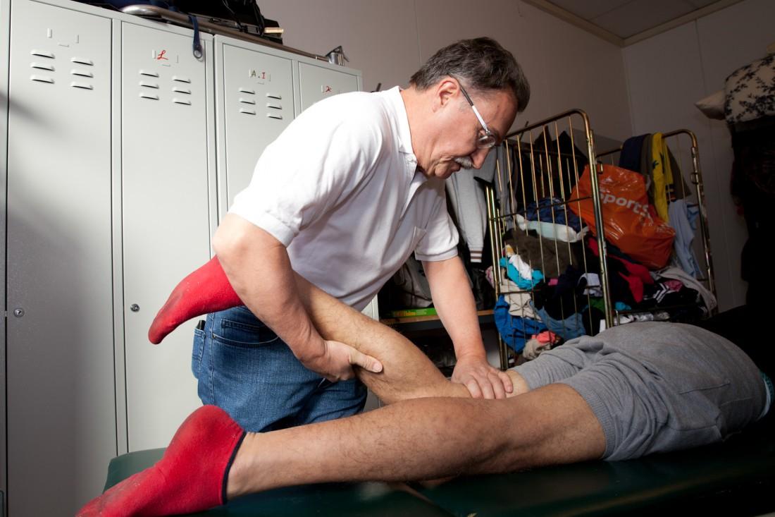 Dr. Klaus Burghard prüft das verletzte Bein eines jungen Mannes