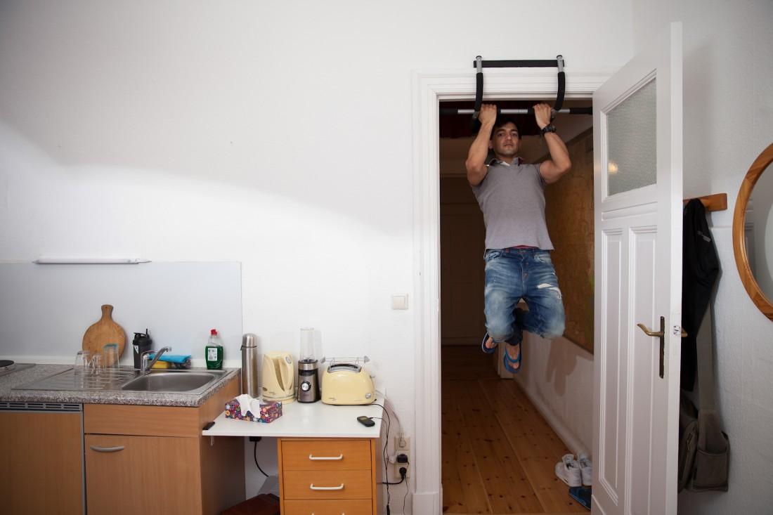Der afghanische Fluechting Rohulla Moradi lebt bei Ehepaar Riedel in Berlin. An seinem Tuerrahmen haengt eine Klimmzugstange an der er taeglich trainiert. (c) 2015 Kathrin Harms und Esteve Franquesa